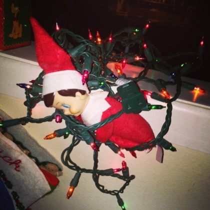 Elf on a Shelf tangled in Christmas lights.